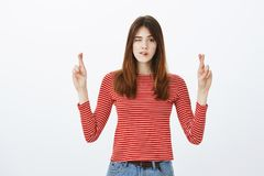 Peeking to see good opportunity for action. Indoor shot of creative good-looking female student raising hands with. Crossed fingers, biting lip and looking with Royalty Free Stock Image