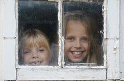 Peeking in window. Little girls peeking in old barn window stock photo