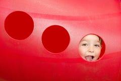 Peeks svegli del bambino attraverso il foro al campo da giuoco Fotografie Stock Libere da Diritti