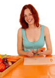 Peel carrots. A young woman peeling a carrot Stock Images