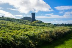 Peel Castle`s tower next to Saint Patrick`s Church at Peel city in Isle of Man Royalty Free Stock Photo