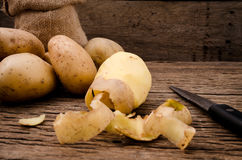 Peel fresh potatoes on rustic wooden background. Raw organic pot. Peel and peeling fresh potatoes Royalty Free Stock Photos