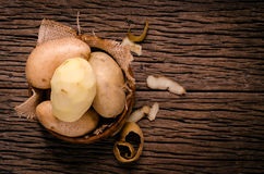 Peel fresh potatoes in wooden bowl. Raw organic potatoes on old. Peel and peeling fresh potatoes royalty free stock images