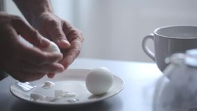 Peel a hard boiled egg with hands. Man peels a hard boiled egg with hands in the morning. He stays near the table, there are cup and coffee pot stock footage