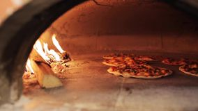 Peel placing pizza baking in oven at pizzeria stock video