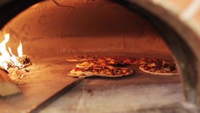 Peel placing pizza baking in oven at pizzeria stock footage
