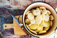 Peeled切了在一个罐的土豆在石桌背景  免版税库存照片