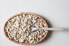 Peeled посолил арахисы в плетеной корзине и деревянной ложке на беже Стоковая Фотография RF