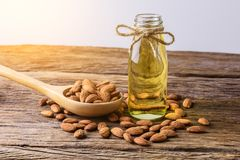 Peeled almonds with bowl and Bottle of almond oil on rustic wood. En background Stock Photography