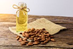 Peeled almonds with bowl and Bottle of almond oil on rustic wood. En background Stock Photos