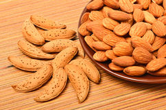 Peeled almonds on the ceramic saucer and in the nutshell. On the wooden background Stock Images