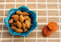 Peeled almonds and a couple of dried fruit apricots. Stock Image
