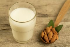 Peeled almonds and a glass of milk on wooden table Royalty Free Stock Images