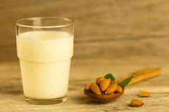 Peeled almonds in a spoon  and a glass of milk on wooden table Royalty Free Stock Photography