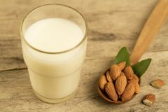 Peeled almonds in a spoon and a glass of milk on wooden table Stock Photo