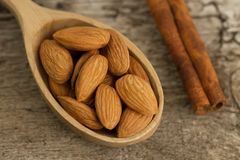 Peeled almonds in spoon on wooden background Stock Photography