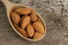 Peeled almonds in spoon on wooden background Stock Images