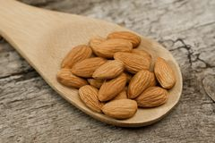 Peeled almonds in spoon on wooden background Royalty Free Stock Photos
