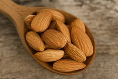 Peeled almonds in spoon on wooden background Royalty Free Stock Image