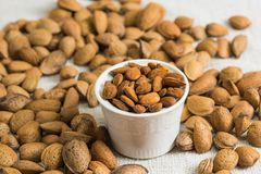 Peeled almonds in a white bowl and nutshell around on beige fabric texture. Background of nuts. Peeled almonds in a white bowl on beige fabric texture. Nutshell stock image