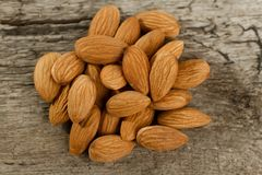 Peeled almonds on wooden background Stock Photos