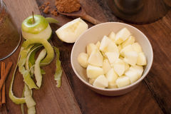 Peeled apple beside chopped pieces in bowl Royalty Free Stock Images