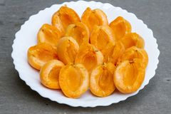 Peeled apricot on a plate. Peeled fresh apricot on a white plate without pits. Healthy and natural food. stock photo