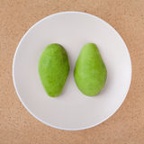 Peeled avocado. Fresh peeled halved avocado on plate, over wooden background Royalty Free Stock Image