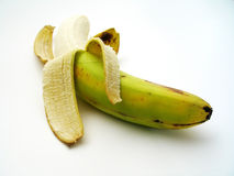 Peeled Banana. A partially ripe banana, skin peeled back, focus mainly on the bottom of the royalty free stock images