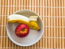 Peeled banana and apple inside white bowl. Healthy snack of banana and apple inside white bowl on wooden table Royalty Free Stock Photo