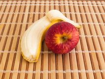 Peeled banana and apple on wooden table. Healthy eating, banana and apple breakfast on wooden table in bright morning Stock Photo