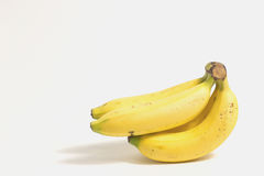 Peeled banana near a cluster of ripe bananas on white background. Royalty Free Stock Image