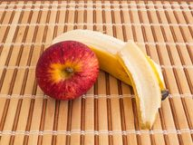Peeled banana and red apple on wooden slats. Peeled banana and red apple fruits viewed from the top on wooden slat table, in a healthy and natural diet Royalty Free Stock Images