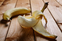 Peeled banana on a rustic table Royalty Free Stock Image