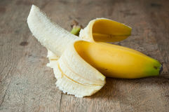 Peeled banana on wooden background Stock Image