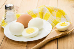 Peeled boiled eggs in white plate, salt and bamboo spoon Stock Images