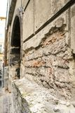 Peeled Brick Wall in Age-old House with Door Arch. Closeup ancient broken peeled brick wall in age-old house with door arch in old european city Stock Photo