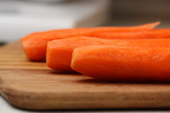 Peeled carrots on wooden chopping board. Stock Photos