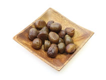 Peeled chestnut on a wooden plate Royalty Free Stock Photography