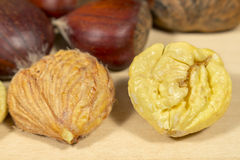 Peeled chestnuts beside other ones in shell, on a wooden table Stock Image