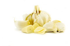 Peeled chopped garlic. Peeled chopped fresh garlic cloves and unpeeled cloves, isolated on a white background Royalty Free Stock Image