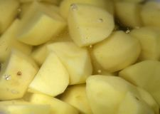 Peeled and Chopped Potatoes Underwater. Peeled and chopped potato pieces underwater. There is some little bubbles. Cooking process of mashed potatoes. Color royalty free stock images