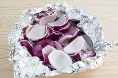 Peeled and chopped red onions in tin foil. Fresh peeled and chopped red onion slices in tin foil Royalty Free Stock Images