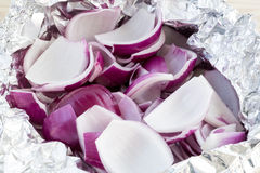 Peeled and chopped red onions in tin foil. Fresh peeled and chopped red onion slices in tin foil Stock Photo