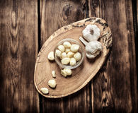 Peeled cloves of garlic on a wooden trunk. Royalty Free Stock Photography