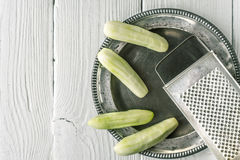 Peeled cucumbers in the metal plate with grater horizontal Stock Photography