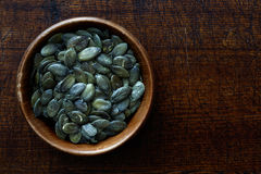Peeled dry pumpkin seeds in dark wooden bowl isolated on dark br Stock Image