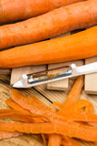 Peeled fresh raw carrots with peeling knife.  Royalty Free Stock Images