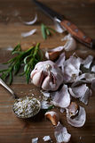 Peeled Garlic Bulb, Rosemary and Salt on a Kitchen Table Royalty Free Stock Photo