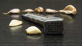 Peeled garlic clove and garlic press. Peeled garlic clove and garlic press on a garlic table background Royalty Free Stock Photography